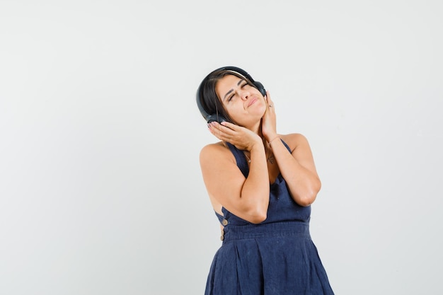 Young lady in dress enjoying music with headphones and looking delighted