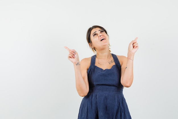 Giovane donna vestita che punta in alto e sembra concentrata