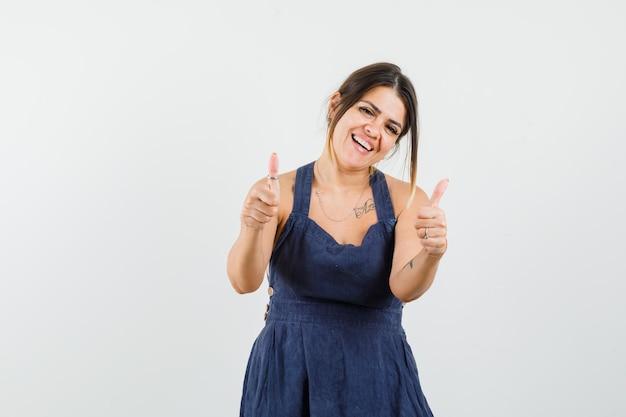 Giovane donna in abito che mostra il doppio pollice in alto e sembra allegra