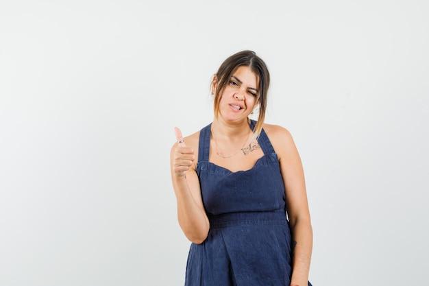 Giovane donna in abito che mostra pollice in su, strizzando l'occhio