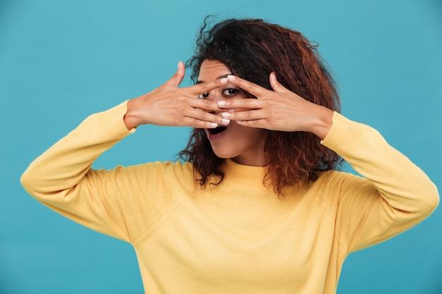 Giovane donna vestita in maglione caldo che copre il viso con le mani.