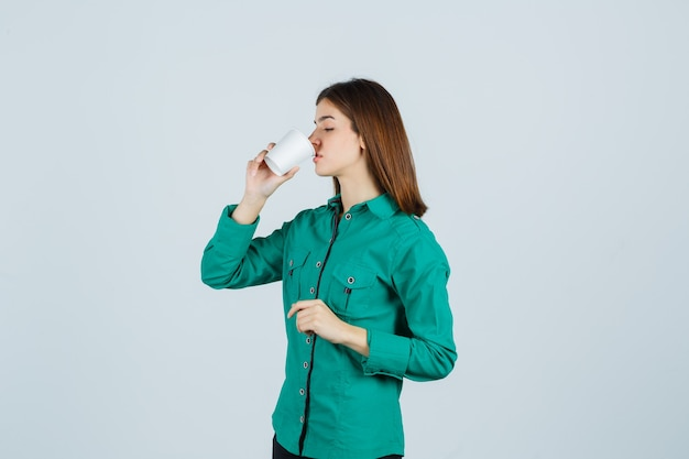 Young lady drinking coffee from plastic cup in shirt and looking focused. front view.