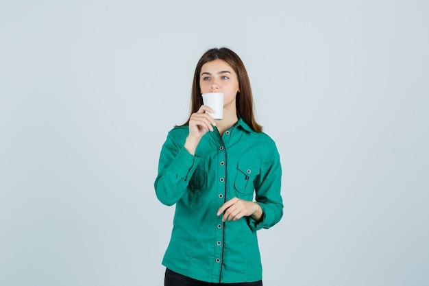 Giovane signora che beve caffè dal bicchiere di plastica in camicia e guardando pensieroso, vista frontale.