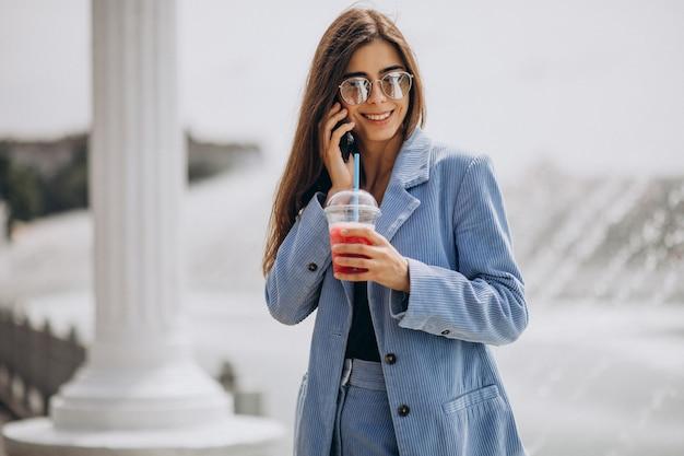 公園でアイスティーを飲むと電話で話している若い女性