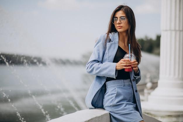 Девушка пьет чай со льдом в парке