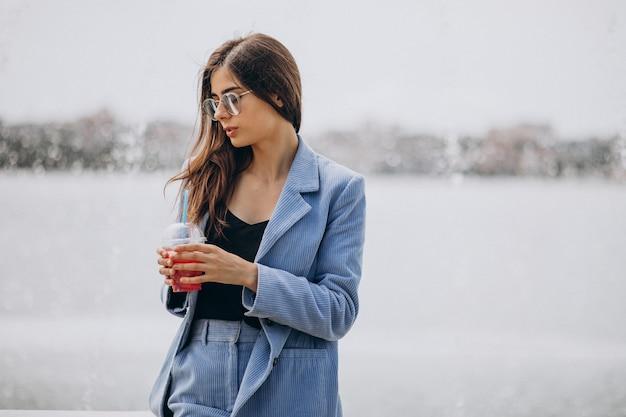 公園でアイスティーを飲む若い女性