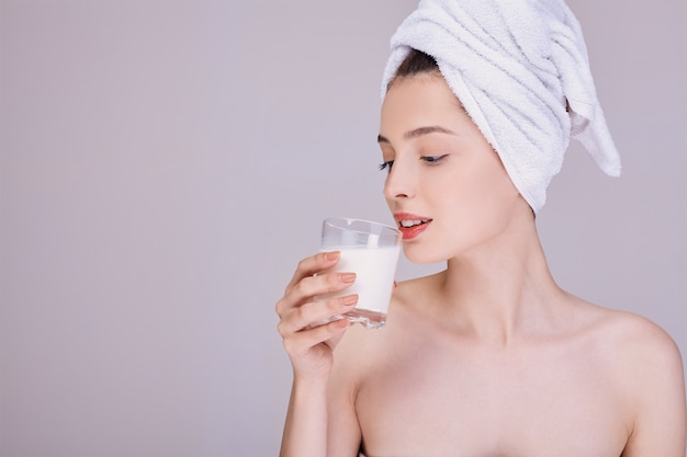 A young lady drinks milk after a shower.