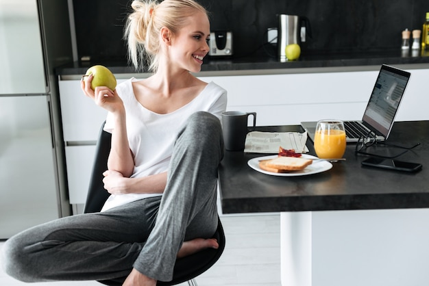 Young lady eating apple and using laptop in kitchen
