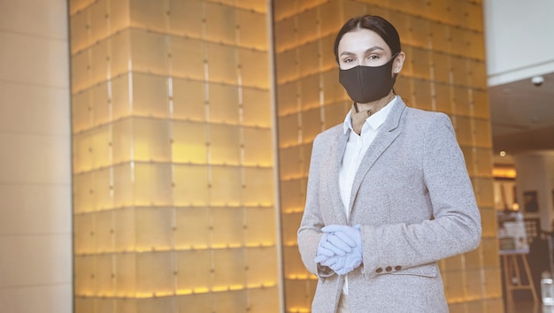 Young lady in elegant suit standing in the hall with a mask on her face and rubber gloves on hands. website banner