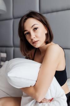 Giovane signora che abbraccia il suo cuscino al mattino nella sua camera da letto a casa