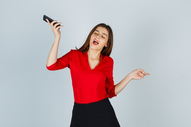 Young lady enjoying while holding mobile phone in red blouse, skirt and looking amused