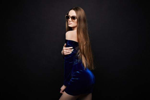 Young lady in fashionable blue dress with naked shoulders and stylish leopard sunglasses posing at the studio