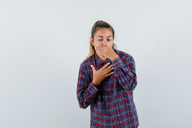 Young lady feeling nauseated in checked shirt and looking unwell. front view.