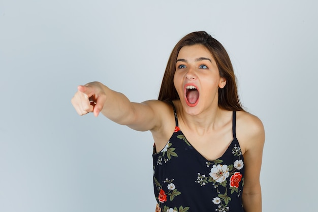 Young lady in floral top pointing at someone while shouting and looking resentful