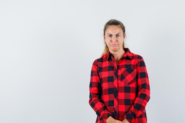若い女性は顔をしかめ、チェックのシャツで唇を湾曲させ、疑わしい顔をしています