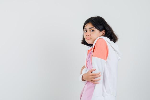 ジャケット、ピンクのシャツで寒くなり、かっこよく見える若い女性。 無料写真
