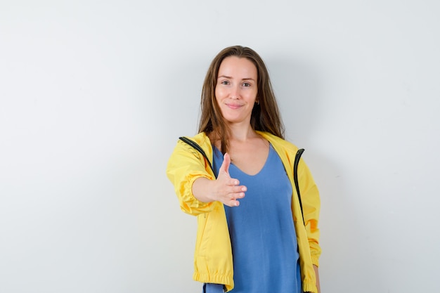 Молодая дама протягивает руку для тряски в футболке и выглядит нежной. передний план.