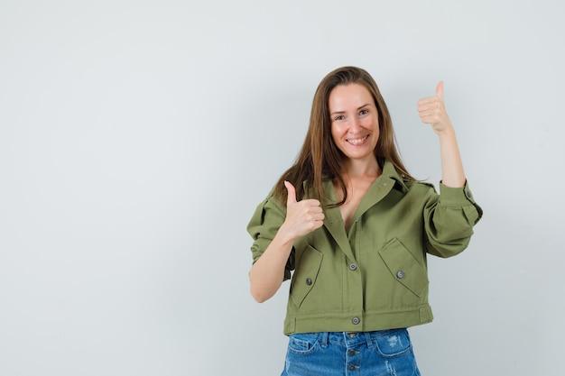 Giovane donna in pantaloncini giacca verde che mostra i doppi pollici in su e sembra allegra