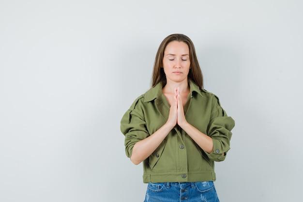 Giovane donna in giacca verde, pantaloncini che mostrano il gesto di namaste e che sembra calma, vista frontale.