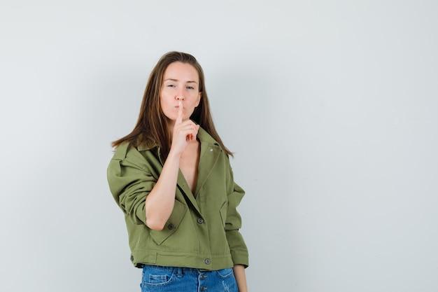 Giovane donna in giacca verde, pantaloncini che mostrano gesto di silenzio e guardando attento, vista frontale.
