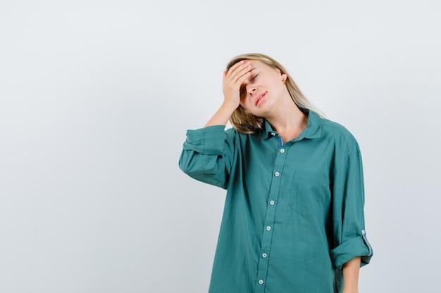 Giovane donna in camicia verde che tiene la mano sulla fronte e sembra serena