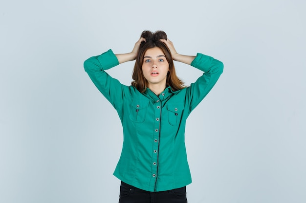Young lady in green shirt holding hands on head and looking bewildered , front view.