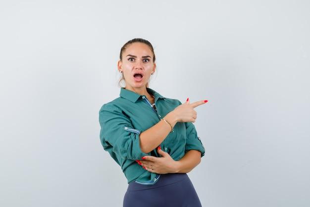 Giovane donna in camicia verde che punta a destra e sembra scioccata, vista frontale.