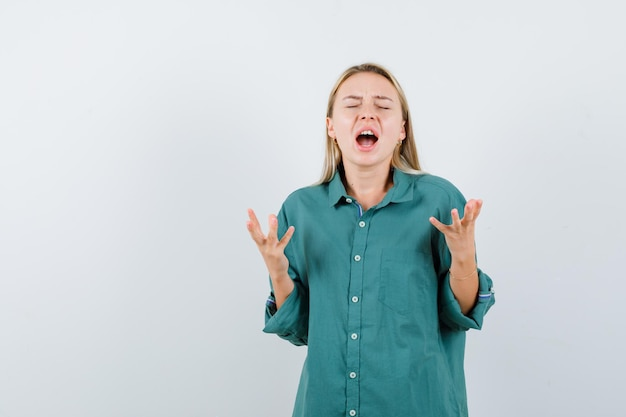 Young lady in green shirt raising hands in aggressive manner and looking wistful