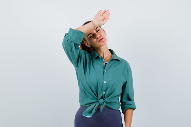 Young lady in green shirt suffering from headache and looking fatigued , front view.
