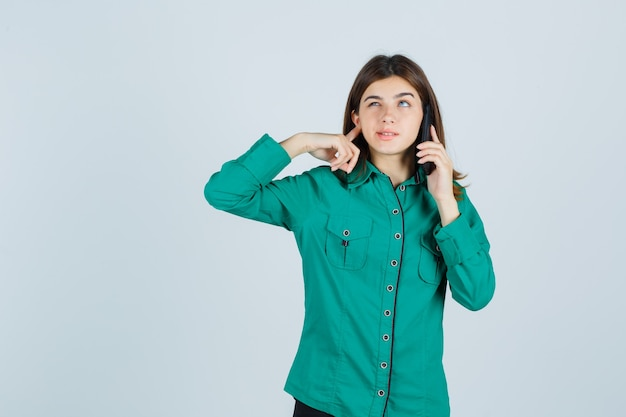 Young lady in green shirt talking on mobile phone, plugging ear with finger and looking confused , front view.