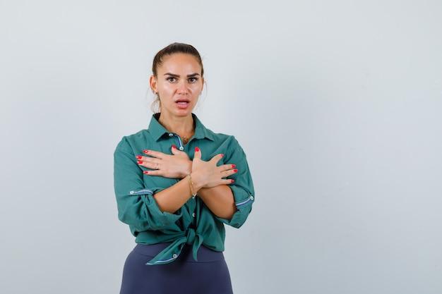 Giovane donna in camicia verde con le mani incrociate sul petto e dall'aspetto spaventato, vista frontale.