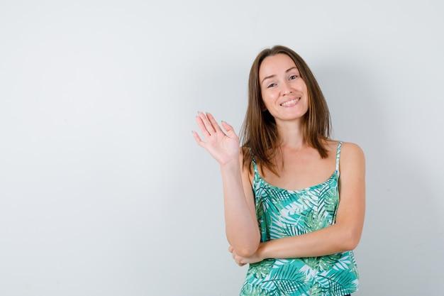 開いた手で挨拶し、陽気に見える若い女性、正面図。