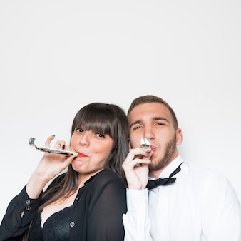 Young lady and guy in evening wear with party flutes