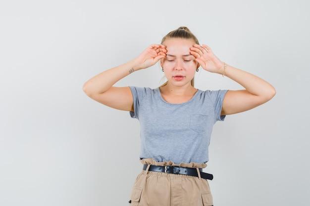 젊은 아가씨 t- 셔츠, 바지에 두통이 있고 피곤, 전면보기를 찾고.