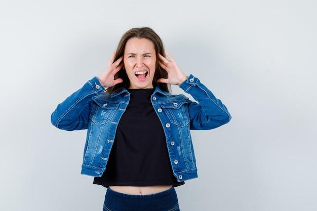Молодая леди с проблемой громкого шума в блузке, куртке и растерянным видом, вид спереди.