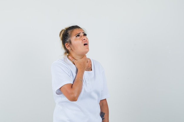 Young lady having sore throat in t-shirt and looking unwell