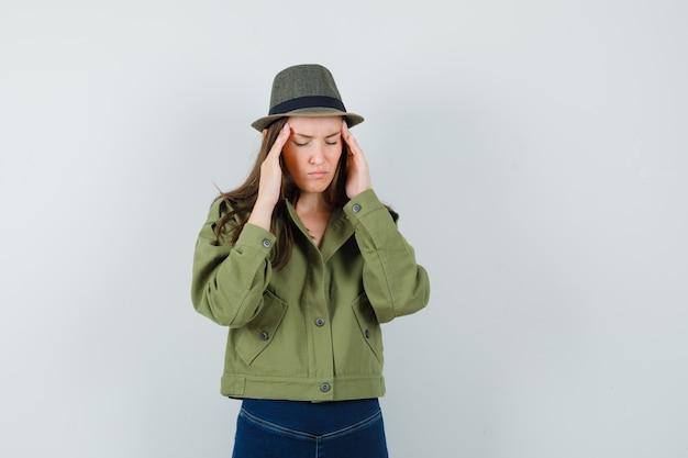 ジャケットパンツの帽子に強い頭痛があり、疲れている若い女性