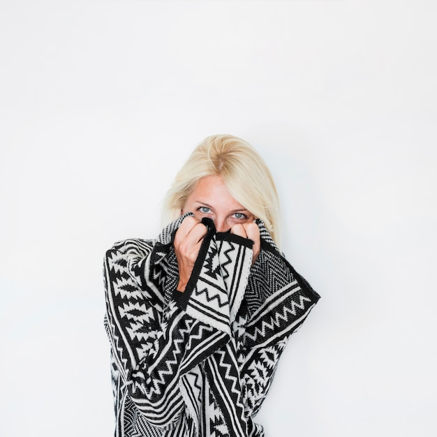 Young lady hiding face behind patterned apparel