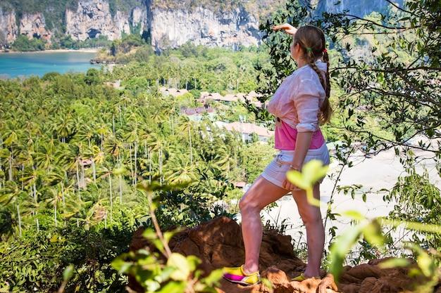 젊은 여성 등산객 머리 땋은 산 꼭대기에서 열대 해변의 전망을 즐기는 모습