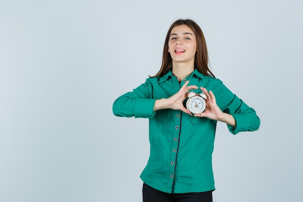 Young lady holding alarm clock in shirt and looking pretty. front view.