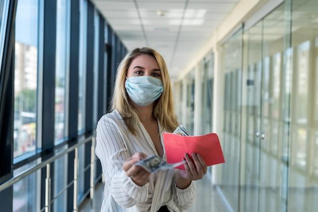 Девушка держит конверт и считает доллары на работе. концепция взятки