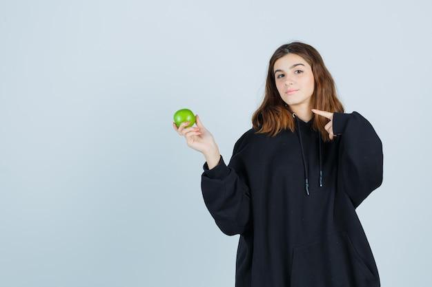 Девушка держит яблоко, указывая на левую сторону в огромной толстовке с капюшоном, штанах и выглядит симпатично. передний план.