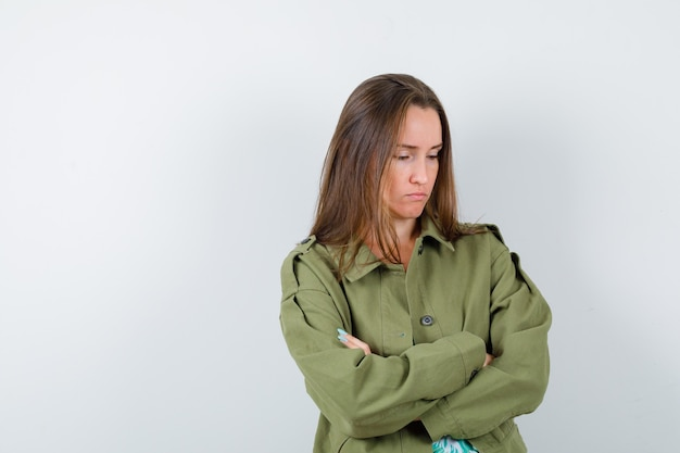 팔짱을 끼고 녹색 재킷을 입고 화난 표정을 한 젊은 여성이 정면을 바라보고 있습니다.