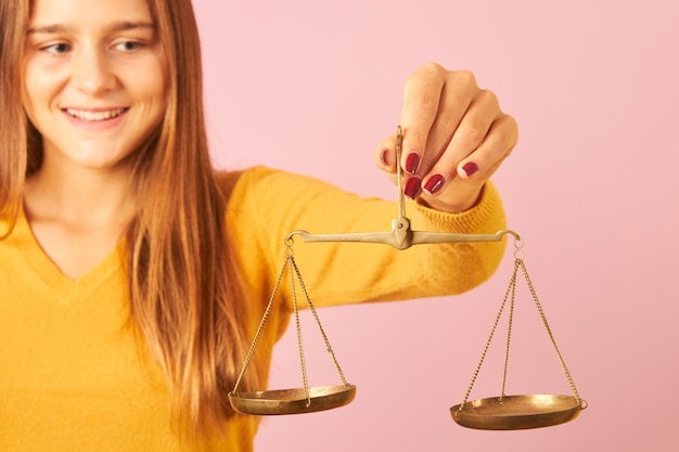 Young lady holding a balance on pink