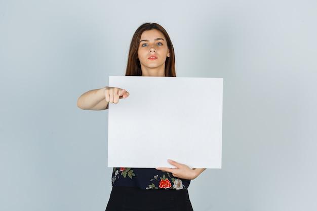 Молодая дама держит чистый холст, указывая на камеру в блузке, юбке и выглядит серьезно. передний план.