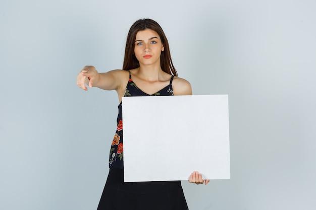 Giovane donna che tiene una tela bianca, che punta via in camicetta, gonna e sembra seria. vista frontale.