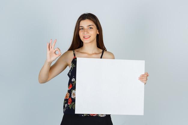 Giovane donna che tiene una tela bianca, che mostra un gesto ok in camicetta, gonna e sembra allegra. vista frontale.