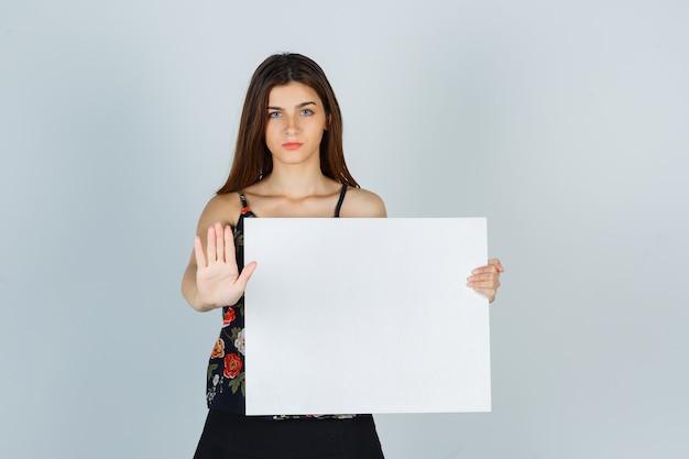 空白のキャンバスを保持し、ブラウス、スカートで停止ジェスチャーを示し、真剣に見える、正面図の若い女性。