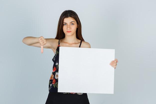 Giovane donna che tiene in mano una tela bianca, che mostra il pollice in giù in camicetta, gonna e sembra dispiaciuta. vista frontale.