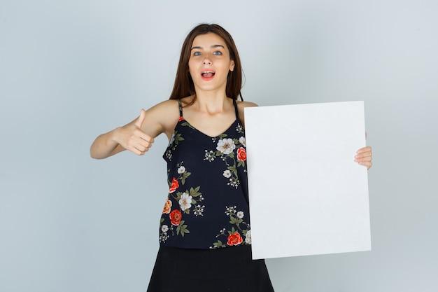 Giovane donna che tiene tela bianca, mostra il pollice in camicetta, gonna e sembra allegra. vista frontale.